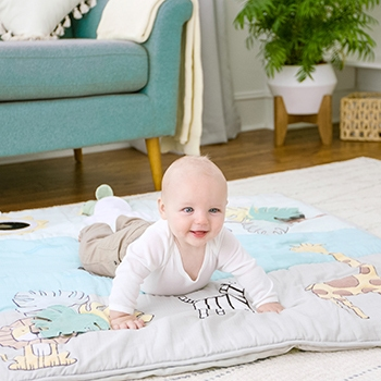 Baby lies on Aden and Anais Blanket