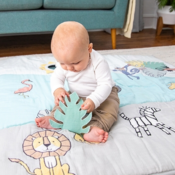 A baby examines a blanket Aden and Anais - Aden and Anais