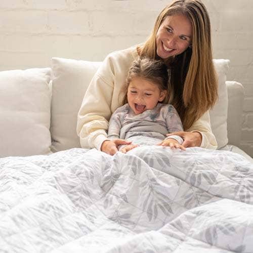 maman joue avec sa fille sous le couverture lestée