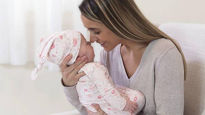 maman avec bébé portant aden + anais coffret-cadeau nouveau-né combinaison + bonnet à nouer maille confort 0-3 mois